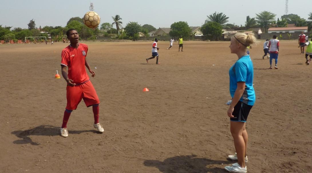 Voluntaria entrena en fútbol a un adolescente en Ghana.